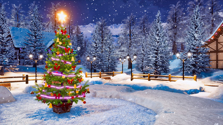 Outdoor Christmas tree decorated by lights garland against snow covered alpine mountain village on background at snowfall winter night. Imagens