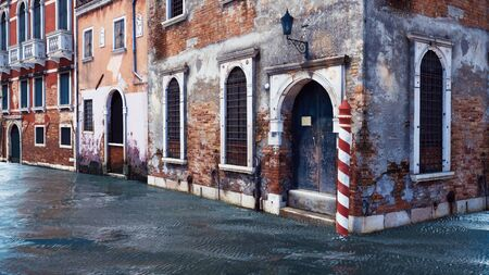 Ancient venetian buildings with cracked exterior walls and arched windows along the water canal in Venice, Italy. With no people realistic 3D illustration from my own 3D rendering file.