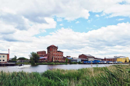 Old paper mill factory complex with mostly abandoned buildings in industrial zone on riverbank of city river in Kaliningrad, Russia (formerly german Koenigsberg) at daytime Stock Photo