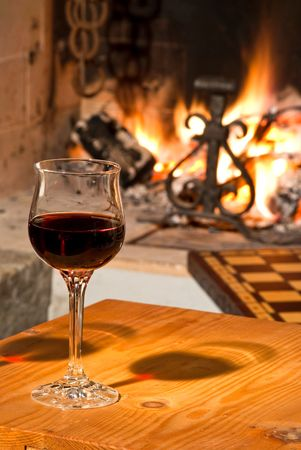 Fireplace & glass of red wine photo