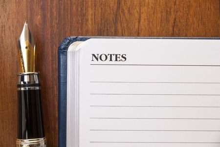 listings: fountain pen and blank diary over a wooden desk