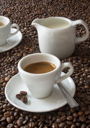 immersed: a white coffee cup of espresso over many coffee beans Stock Photo