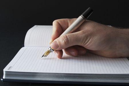 escribiendo: escribir o la firma en un orden del d�a en blanco Foto de archivo