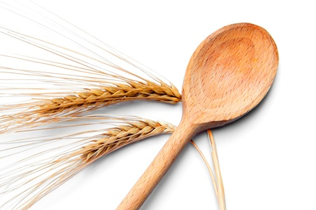 ear of wheat and wooden spoon isolated on white background photo