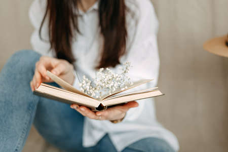 A close-up photo of an open book on the sheets of which white small flowers lie, and the girl's fingers turn over the book. No face, only part of the figure. Literature. Mood.