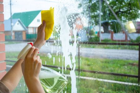 The girl washes the windows with a rag and a special means. Dirty windows that need to be washed. The girl cleans the house