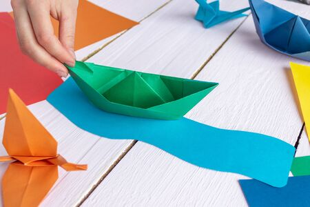 The girl is playing with origami of a paper boat that she made herself. On a wooden background
