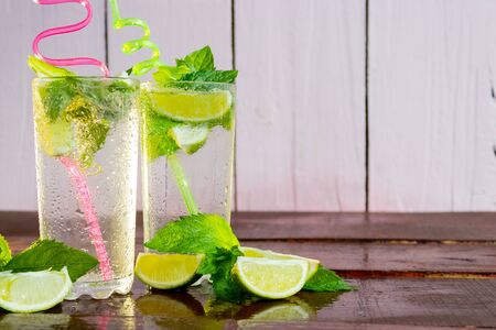 A refreshing drink in the summer heat is a Mojito. Two glasses of fresh Mojito. Lime and mint. On a wooden background