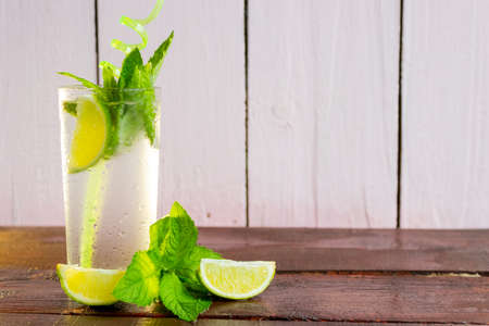 A glass of fresh Mojito. Lime and mint. On a wooden background