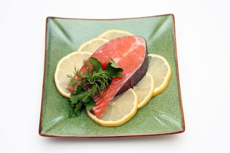 garnishments: salmon with lemon and parsley on plate isolated on white background Stock Photo