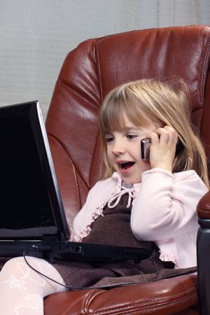 Little business girl with a notebook, speaks by phone photo