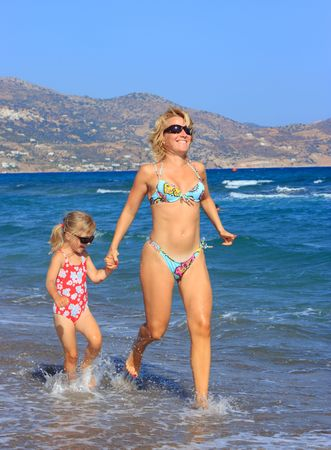 Mother and daughter running on beach photo
