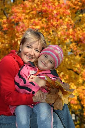 Happy mum with a daughter in autumn park photo
