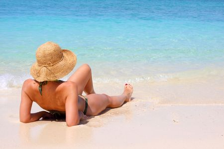 qua: woman sitting on a tropical beach