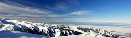 Snow covered mountains and lake Issyk Kul, panoramic photo
