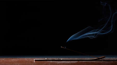 Incense stick on a table with black background peacefully burns in silent