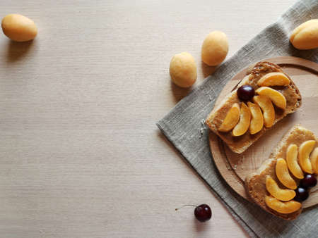 vegetarian breakfast on a wooden board, bread with condensed milk and apricots. horizontal photo with copy space