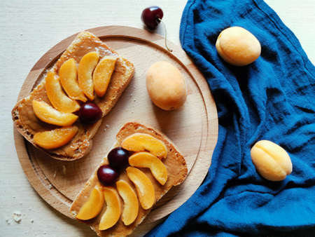 breakfast on a wooden board sweet bruschetta with condensed milk and apricots. horizontal photo top view Reklamní fotografie