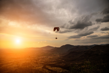 paraglider: People fly a paraglider on a background of beautiful scenery. Stock Photo