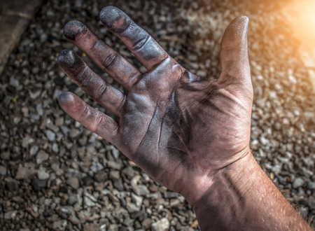 cupped: Caucasian hands cupped with black heavy fuel Stock Photo