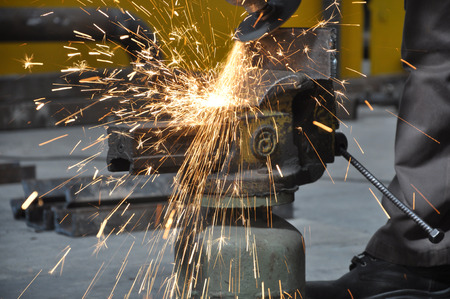 tool and die: Electric wheel grinding on steel structure in factory Stock Photo