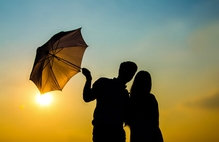 couple lit: Umbrella couple love stand and sunset silhouette