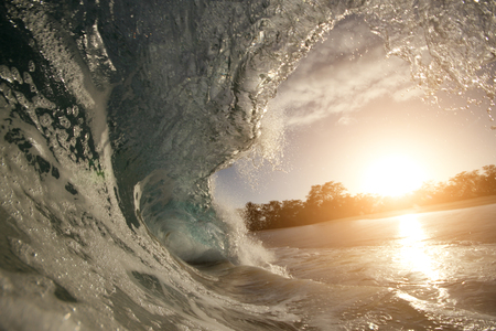 breaking down: rough colorful ocean breaking surf wave falling down at sunset time Stock Photo