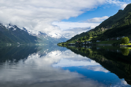 hardangerfjord: Brilliant landscape view on the mountain peaks with green slopes and the mirror surface of the water and wonderful feather clouds on the sky on background, Norway, Hardangerfjord