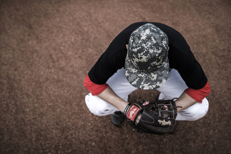 baseball dugout: Baseball player sitting on his haunches, top view. Stock Photo