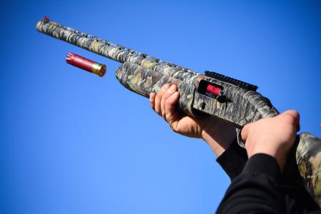 Camouflage shotgun. Casing flies out of a shotgun