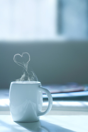 Cup of coffee with steam in heart shape