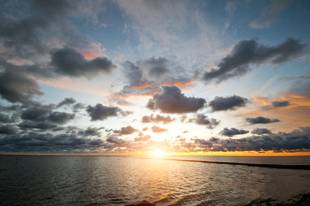 Beautiful scenic landscape with dramatic cloudy sky at sunset and a sun glade on a ripple sea water Stock Photo