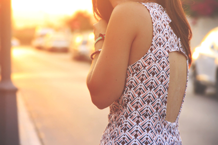 A woman is standing back in a dress with cutouts on the back on a background of the suns rays