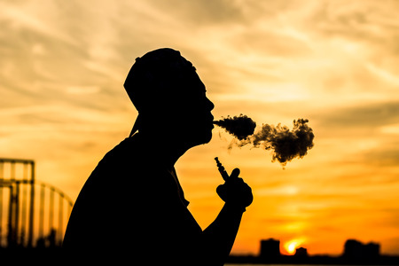 drug user: Silhouette of a vaper produces dads (smoke )