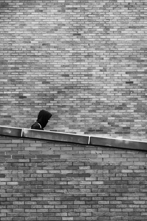 goes: The man in the hood goes down the slope on a background of a brick wall