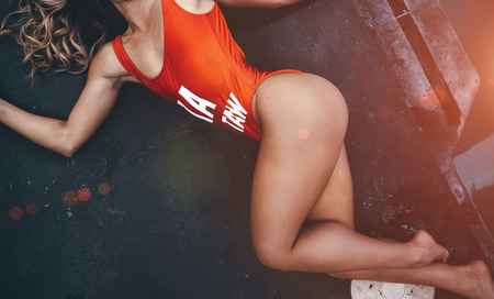 Sexy woman in red body lies in a beautiful pose