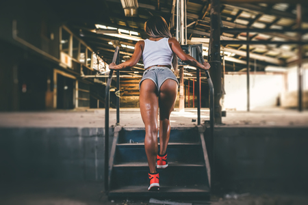 Fitness sexy woman with beautiful ass in shorts walks up the stairs at a construction site Stock Photo