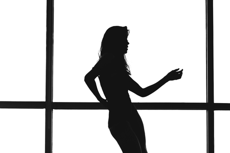 Silhouette of a woman dancing on a white background window Stock Photo