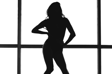 Silhouette of a woman posing in white glass