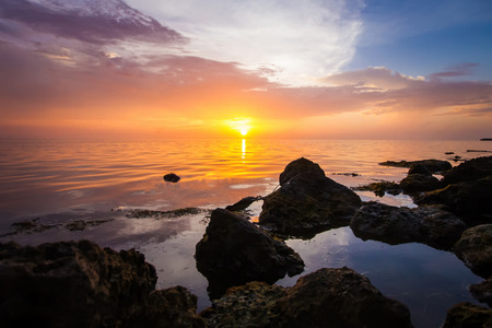 Rocky beach with calm sea during the sunset.