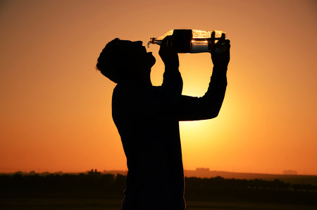 Silhouette of a man drinking water from a bottle Stock Photo