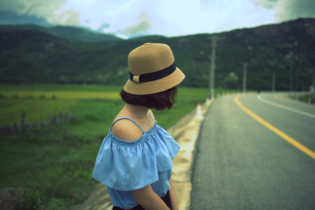 Girl in hat standing near the road side