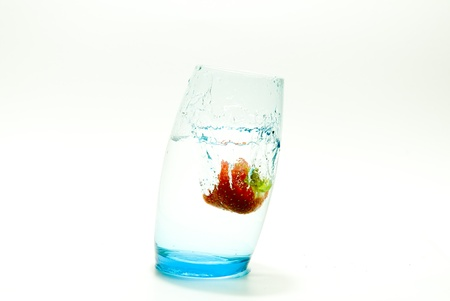 wonky: Strawberry splashing in a glass of water