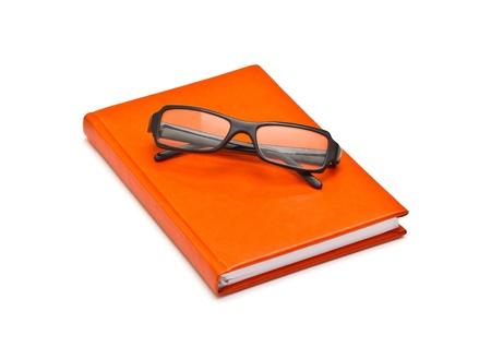 Orange book and glasses, isolated on white background photo