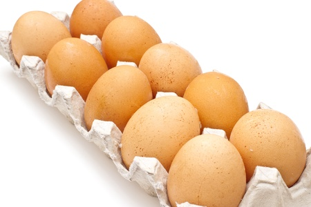 Brown eggs in a carton package on white background photo