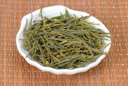 Chinese green tea in plate on bamboo mat photo