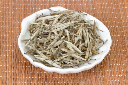 Chinese white tea in plate on bamboo mat photo