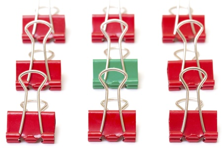 Green paper clip among red  , closeup photo