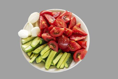 Sliced vegetables - tomatoes, cucumbers and onions on a gray