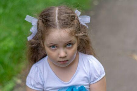 Sad look of little girl outdoor.